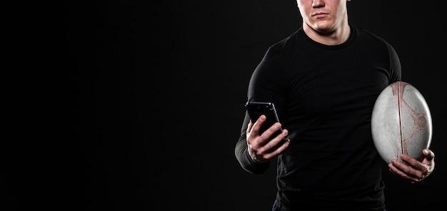 Jogador de rúgbi usando smartphone enquanto segura uma bola com espaço de cópia