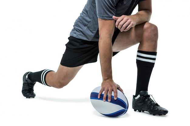 Jogador de rugby em jersey preto alongado com bola