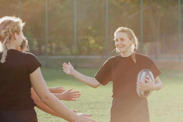 Jogador de rugby feminino saudando seus companheiros de equipe
