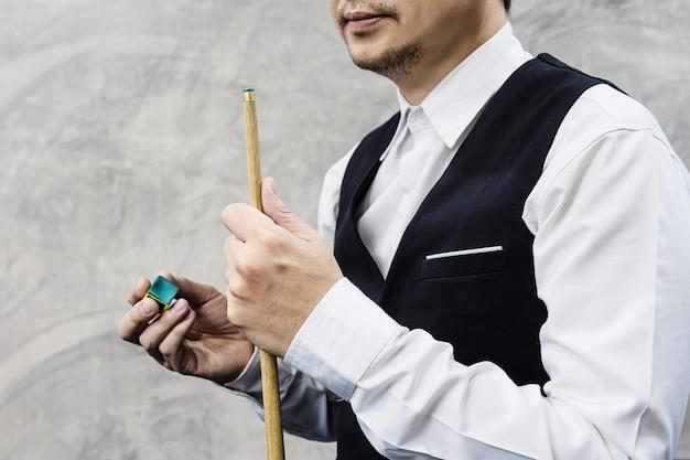 Jogador de snooker em pé espera segurar seu taco e giz