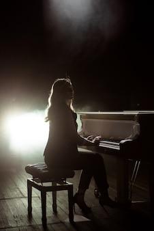 Jogador de teclados feminino no palco durante o concerto, luz de fundo