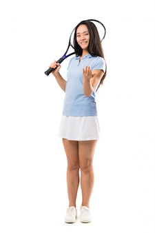 Jogador de tênis asiático novo sobre a parede branca isolada que convida para vir com mão. feliz que você veio