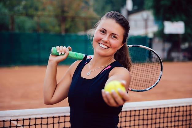 Jogador de tênis. atraente, mulher ativa, ficar, ligado, a, corte, com, raquete tênis, e, bola