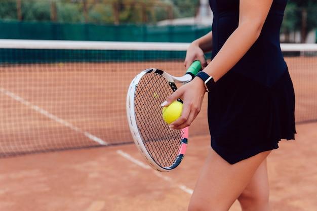 Jogador de tênis. foto de close-up da mulher de atleta no sportswear segurando a raquete e bola