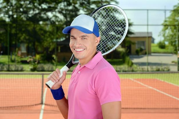 Jogador de tênis que levanta na frente de uma corte de tênis.