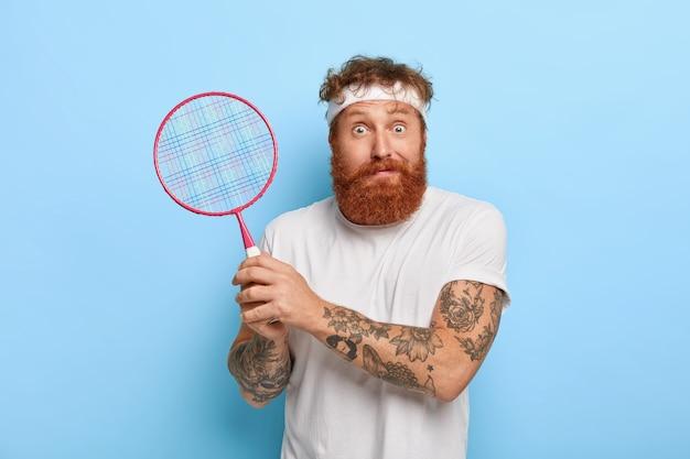 Jogador de tênis ruivo surpreso e concentrado segurando a raquete enquanto posa contra a parede azul