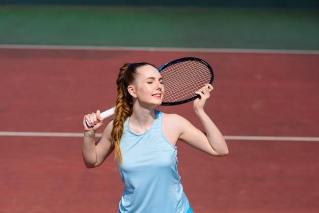 Jogador de tênis sexy garota segurando a raquete de tênis na quadra. jovem mulher está jogando tênis.