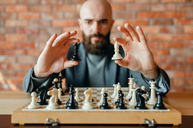 Jogador de xadrez masculino detém figuras brancas e pretas, vista frontal.