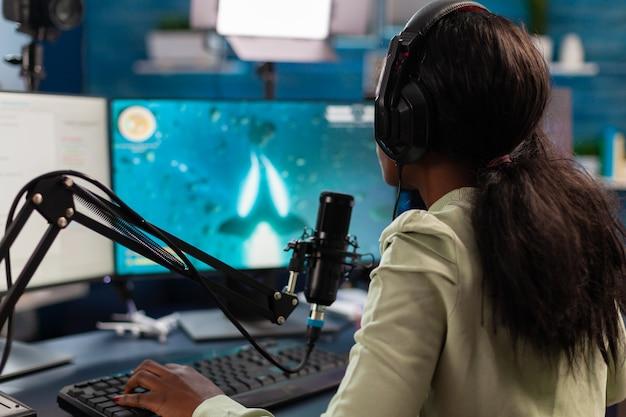 Jogador esportivo africano conversando com colegas de equipe durante a competição de atiradores espaciais com transmissão ao vivo transmitindo videogames virais para se divertir usando fones de ouvido e teclado para campeonatos online.