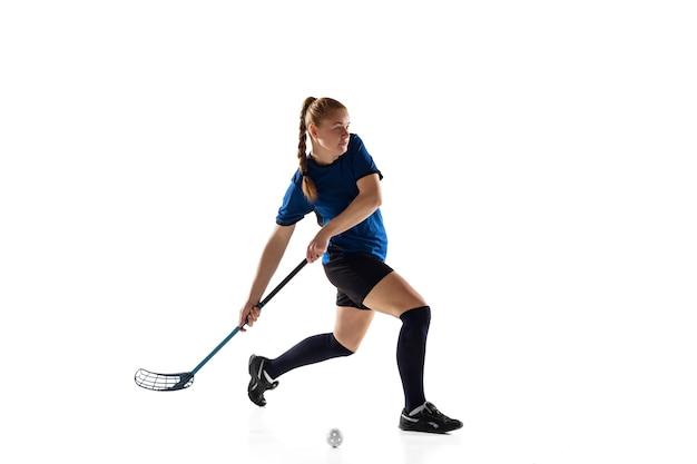 Jogador feminino de floorball isolado no fundo branco do estúdio. ação e movimento, movimento, estilo de vida saudável e conceito de superação. jovem mulher caucasiana em treinamento sportwear, praticando o jogo.