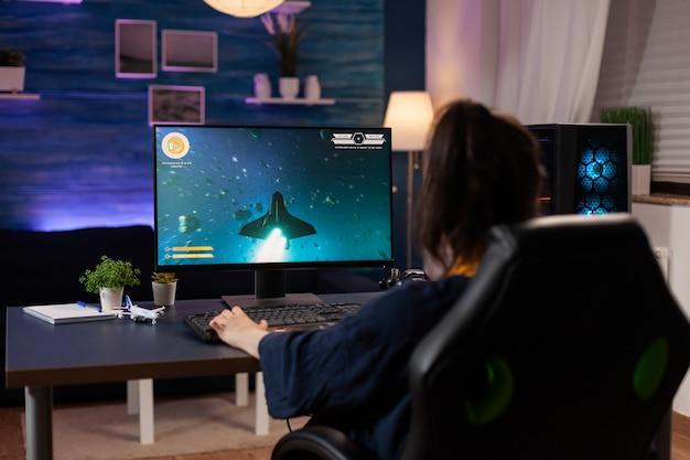Jogador focado sentado em uma cadeira de jogo em home studio e jogando videogames online usando a palavra-chave rgb. jogador profissional profissional fazendo streaming de novos gráficos de videogame online usando um computador poderoso