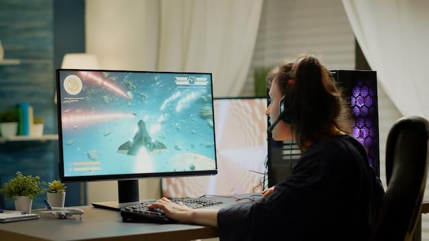 Jogador focado sentado em uma cadeira de jogo jogando videogames de atirador espacial on-line usando a palavra-chave rgb. novos gráficos de videogame profissional de streaming cibernético profissional usando um computador pessoal poderoso