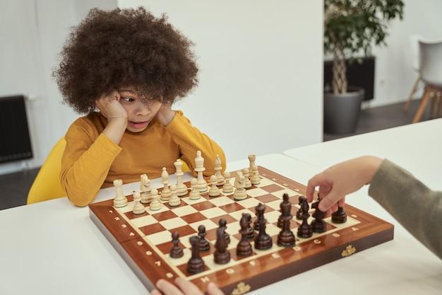 Jogador fofo e engraçado menino com cabelo afro vendo seu amigo se mexendo enquanto joga xadrez