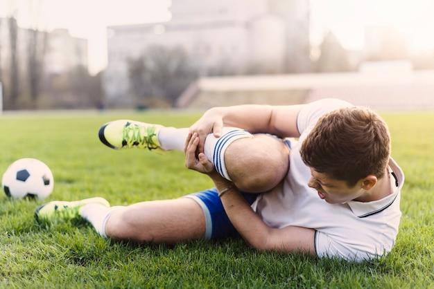 Jogador futebol, segurando, ferido, perna