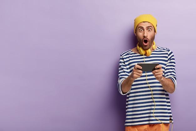 Jogador homem chocado e impressionado joga videogame no smartphone, sendo obcecado por tecnologias modernas