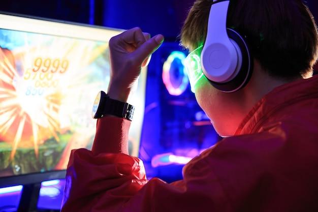 Jogador jogando jogo online no pc na sala escura.