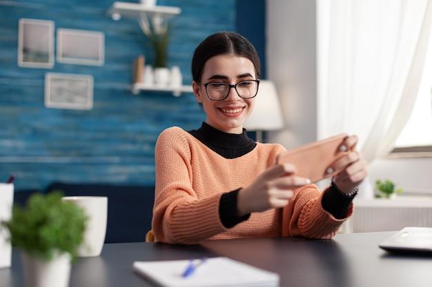 Jogador jogando videogames de entretenimento online com multiplayer durante a competição do ciberespaço usando a tela isolada do telefone. jogador sentado à mesa na sala de estar segurando o dispositivo no modo horizontal