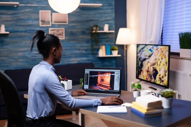 Jogador jovem mulher africana testando jogo profissional online no laptop em casa tarde da noite. jogador profissional verificando videogames digitais em seu computador com rede de tecnologia moderna sem fio.