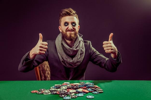 Jogador jovem pocker com polegares para cima