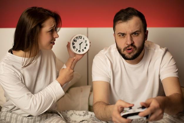 Jogador masculino com joysticks nas mãos, jogando videogame na cama à noite, ignorando a namorada
