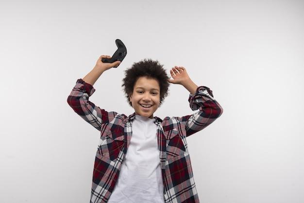 Jogador. menino alegre e feliz sorrindo para você enquanto desfruta de sua vitória