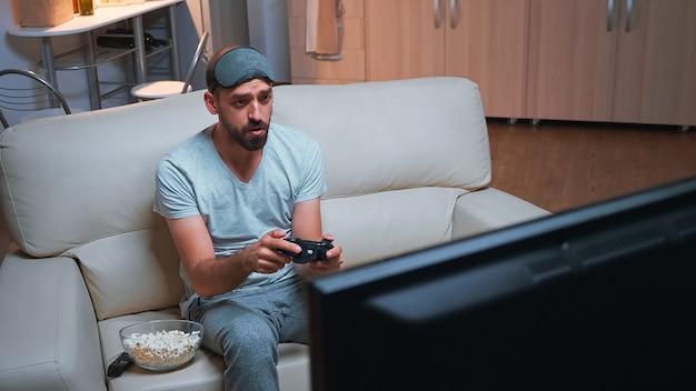 Jogador profissional chateado, perdendo a competição do videogame usando joystick sem fio