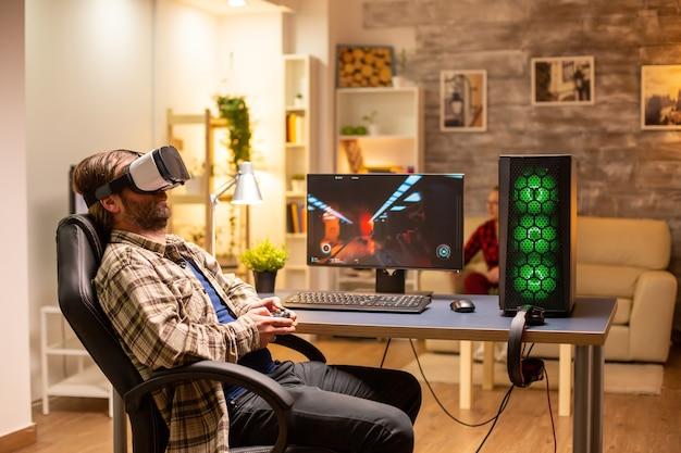 Jogador profissional usando fone de ouvido de realidade virtual para jogar em um pc poderoso tarde da noite em sua sala de estar