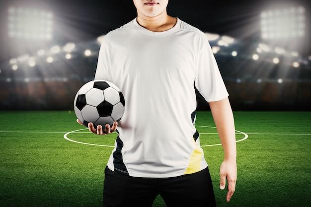 Jogador segurando a bola com o fundo do estádio