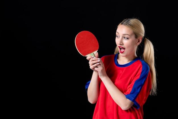 Jogadora com raquete de tênis de mesa em fundo preto.
