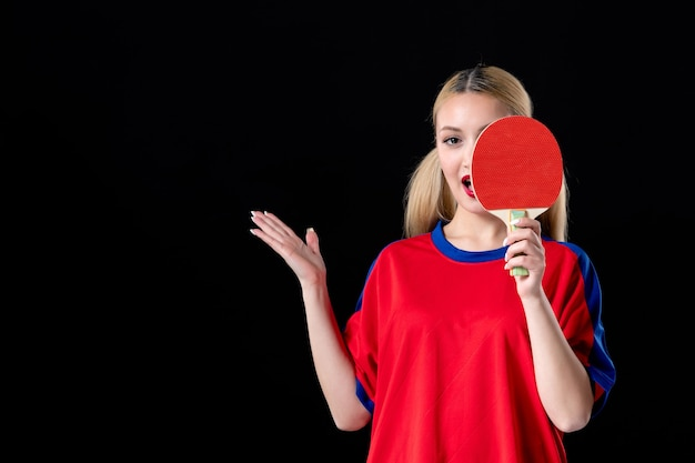 Jogadora com raquete de tênis de mesa no fundo preto jogo de esporte de atleta