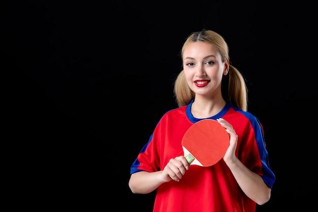 Jogadora com raquete de tênis de mesa no fundo preto.