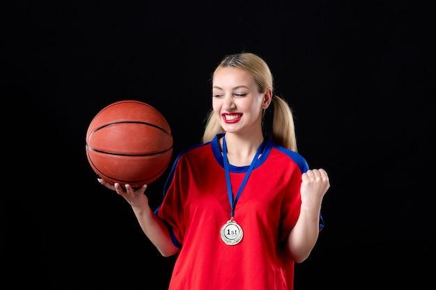 Jogadora de basquete com bola e medalha de ouro no vencedor do troféu de atleta de fundo preto