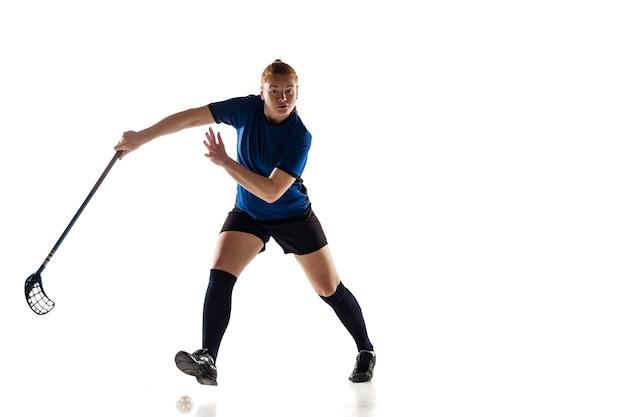 Jogadora de floorball isolada no fundo branco do estúdio, conceito de ação e movimento