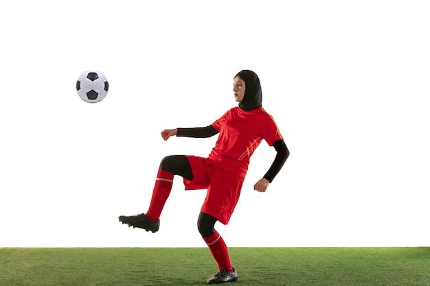 Jogadora de futebol árabe isolada na parede branca do estúdio