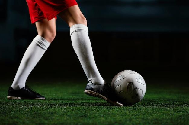 Jogadora de futebol chutando bola perto de você
