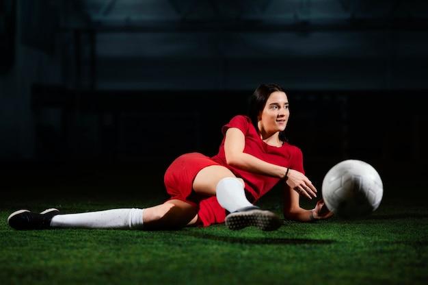 Jogadora de futebol chutando bola