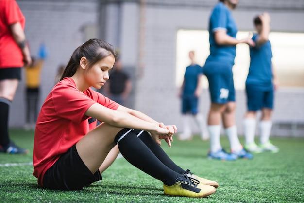 Jogadora de futebol feminino triste ou cansada com uniforme esportivo sentada no campo verde do outro time