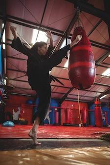 Jogadora de karatê praticando boxe com saco de pancadas