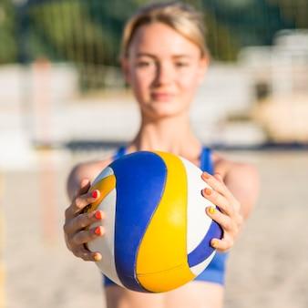 Jogadora de vôlei desfocada na praia segurando uma bola