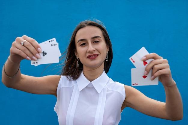 Jogadora segurando cartas de pôquer isoladas sobre fundo azul. jogo