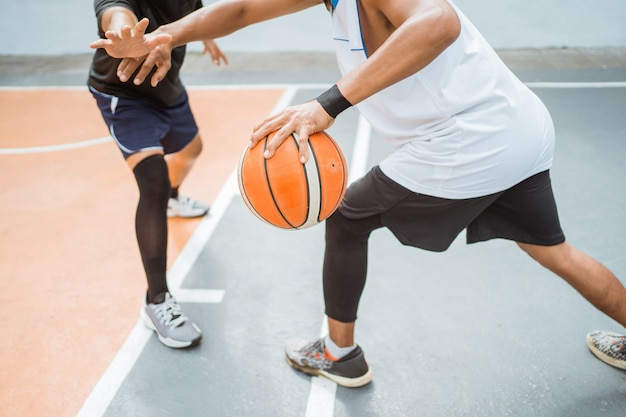 Jogadores de basquete carregando uma bola com a mão em uma técnica de drible alta