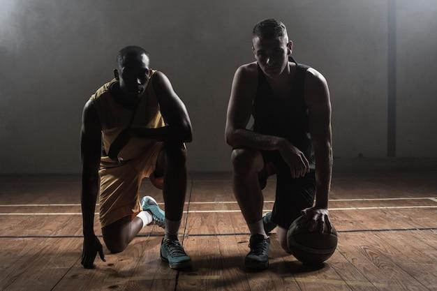 Jogadores de basquete de retrato posando de joelhos
