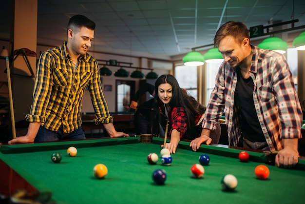 Jogadores de bilhar com tacos na mesa com bolas coloridas