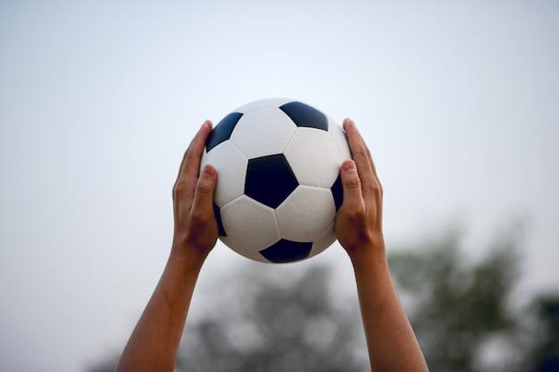 Jogadores de esportes que pegam a bola e o campo de futebol.