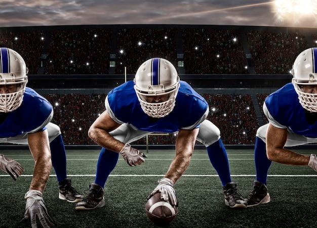 Jogadores de futebol com uniforme azul na linha de scrimmage, em um estádio