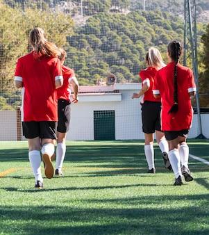 Jogadores de futebol correndo em campo, arremesso completo