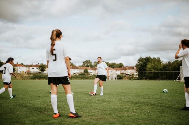 Jogadores de futebol feminino, treinando no campo