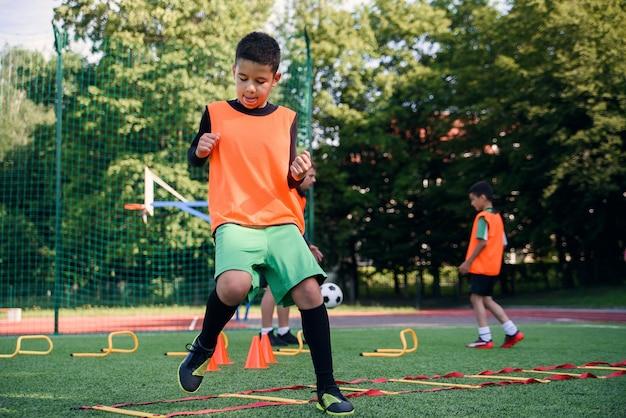 Jogadores de futebol infantil durante o treinamento da equipe antes de uma partida importante. exercícios para os jovens