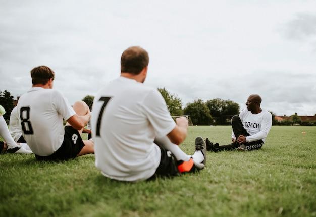 Jogadores de futebol masculino, estendendo-se juntos