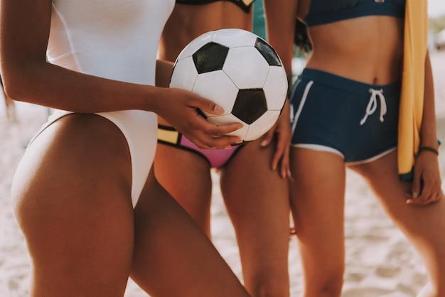 Jogadores de futebol multirraciais recortados da praia das mulheres.